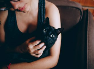person-carrying-black-cat-1123999